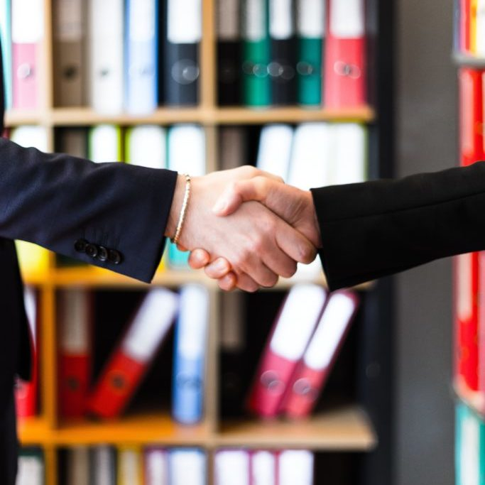 two-person-handshakes-in-front-of-books-on-shelf-2058146